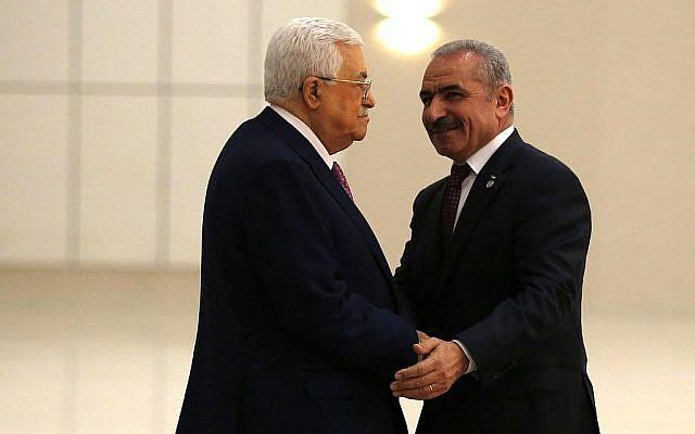 Le président de l'Autorité palestinienne Mahmoud Abbas, à gauche, serre la main du nouveau Premier ministre Mohammad Shtayyeh dans la ville de Ramallah, en Cisjordanie, le 13 avril 2019. (Crédit : Abbas Momani/AFP)