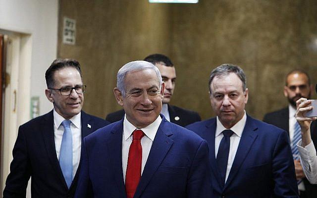 Le Premier ministre Benjamin Netanyahu, au centre, arrive pour la rencontre hebdomadaire de cabinet à son bureau de Jérusalem, le 14 avril 2019 (Crédit : Ronen Zvulun/AFP)