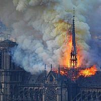 La flèche de la Cathédrale Notre-Dame de Paris, peu avant son effondrement lors de l'incendie qui a touché l'édifice, le 15 avril 2019. (Crédit : Hubert Hitier/AFP)