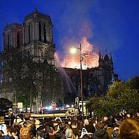 La foule assiste à l'incendie qui ravage Notre Dame de Paris, le 15 avril 2019. (Crédit : ERIC FEFERBERG / AFP)