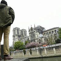 Un homme regarde l'état de la cathédrale Notre-Dame de Paris au lendemain d'un incendie, le 16 avril 2019. (Crédit : Bertrand GUAY / AFP)