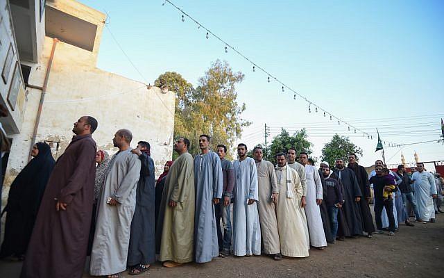Des Egyptiens font la queue devant un bureau de vote pour un référendum sur une révision constitutionnelle controversée dans une école du village de  Saqiyat al-Manqadi, dans la province de Menoufia, au nord du Nil, le 20 avril 2019 (Crédit : MOHAMED EL-SHAHED / AFP)