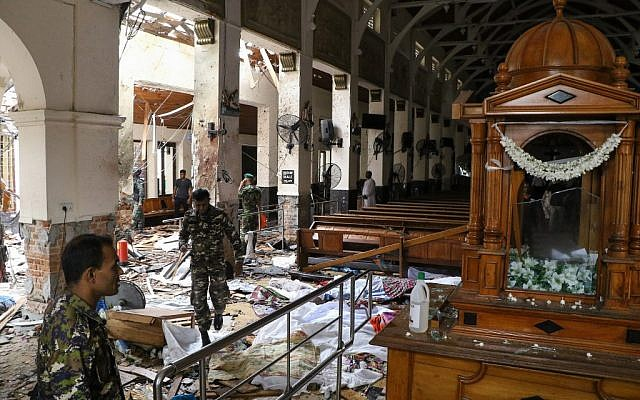 Les personnels de sécurité sri-lankais arpentent une église en évitant les dépouilles, au sol, des victimes qui ont été recouvertes de couvertures parmi les débris d'une explosion survenue au tombeau de Saint-Antoine, à Colombo, le 21 avril 2019 (Crédit :  ISHARA S.  KODIKARA / AFP)