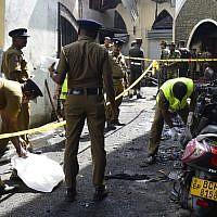 Des membres du personnel de sécurité et des enquêteurs sri-lankais examinent les débris devant l'église de Zion suite à l'explosion survenue à Batticaloa, dans l'est du Sri Lanka, le 21 avril 2019. (Crédit photo : LAKRUWAN WANNIARACHCHI / AFP)