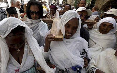 Des pèlerins orthodoxes éthiopiennes transportent une croix dans la Via Dolorosa au cours d'une procession organisée pour le vendredi saint par les chrétiens orthodoxes dans la Vieille Ville de Jérusalem, le 26 avril 2019 (Crédit : PHOTO/GALI TIBBON (Photo by GALI TIBBON / AFP)