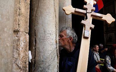 Un pèlerin chrétien orthodoxe porte une croix le long de la  Via Dolorosa pour entrer dans l'église du Saint sépulcre dans la Ville ville de Jérusalem à l'occasion de la procession orthodoxe du vendredi saint, le 26 avril 2019 (Crédit :  GALI TIBBON / AFP)