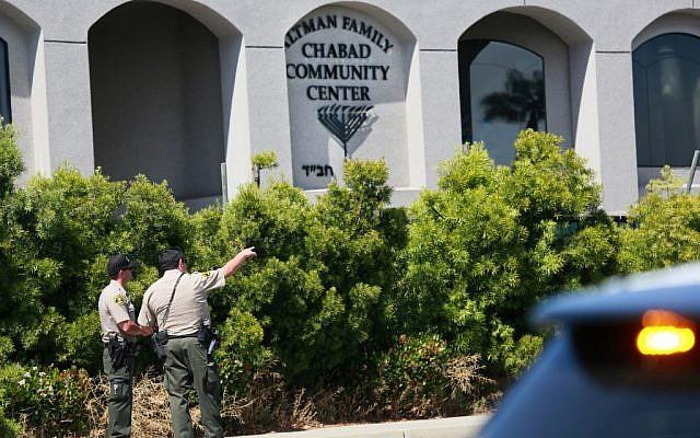 Des adjoints du shérif de San Diego regardent la synagogue de Poway, en Californie, après une fusillade, le 27 avril 2019 (Crédit : SANDY HUFFAKER / AFP)