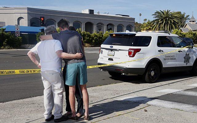 Des gens se réconfortent mutuellement devant la synagogue Habad de Poway, en Californie, qui se trouve de n'autre côté de la rue, après une fusillade, le 27 avril 2019 (Crédit : SANDY HUFFAKER / AFP)