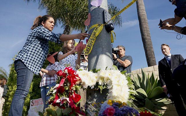 Une femme et une jeune fille placent des papiers sur un petit mémorial dressé face à la synagogue Habad de Poway, en Californie, après une fusillade, le 27 avril 2019 (Crédit : SANDY HUFFAKER / AFP)