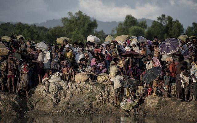 Des réfugiés rohingyas attendent après avoir traversé le fleuve Naf du Myanmar au Bangladesh à Whaikhyang, le 9 octobre 2017. (AFP PHOTO / FRED DUFOUR)