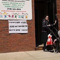 Un panneau mettant en garde contre les symptômes de la rougeole dans le quartier ultra-orthodoxe de Williamsburg, à New York, le 10 avril 2019. (Crédit : Spencer Platt/Getty Images/AFP)