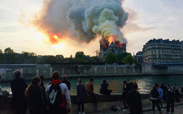 Des Parisiens et des touristes réunis sur les quais de Seine afin d'observer le violent incendie qui a ravagé la cathédrale Notre-Dame de Paris, le 15 avril 2019. (Crédit photo : FOUAD MAGHRANE / AFP)