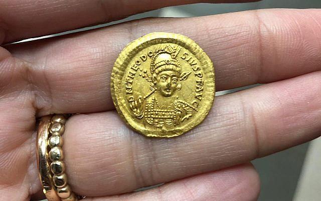 Une pièce rare de l'époque byzantine, vieille de 1600 ans, à l'effigie de l'empereur byzantin Théodose II découvert au mois de février 2019 par des élèves le long de la rivière Zippori en Galilée (Crédit : Nir Distelfeld/Autorité israélienne des antiquités)