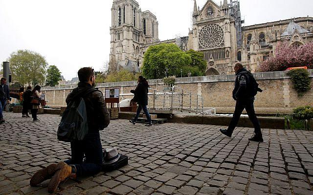 Un homme s'agenouille sur les quais de Seine face à la cathédrale Notre-Dame, le 16 avril 2019. (AP Photo / Christophe Ena)