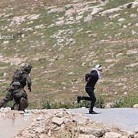 Un soldat de l'armée israélienne pourchasse un suspect palestinien tentant de fuir dans la ville de Tuqu, en Cisjordanie, le 18 avril 2019 (Crédit :Mohammad Hmeid)