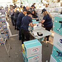 Dés bénévoles de Latet empaquetant des boites pour Pessah. (Crédit photo : Facebook/Latet)