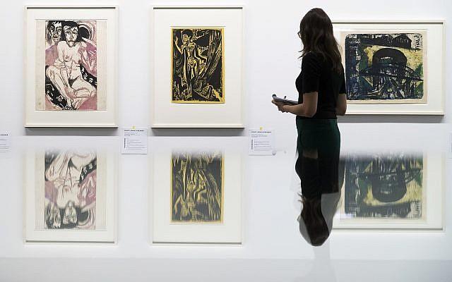 """Une visiteuse observe les œuvres du peintre allemand Ernst Ludwig Kirchner présentées dans l'exposition """"Collection Gurlitt, état des lieux, 'l'art dégénéré' – confisqué et vendu"""" du Kunstmuseum de Berne, en Suisse, novembre 2017. (Crédit : Peter Klaunzer/Keystone via AP)"""