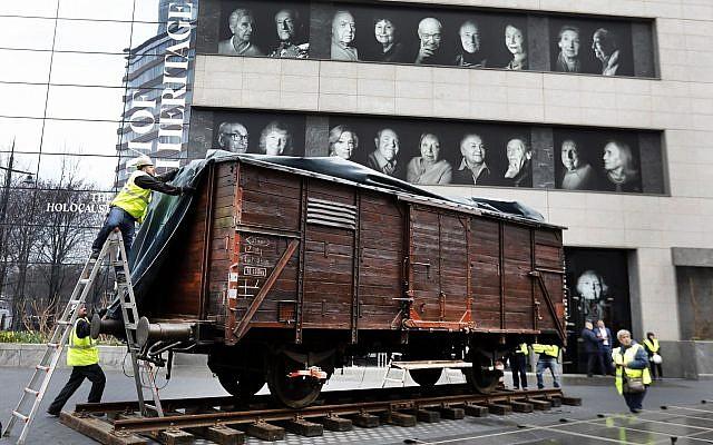 Des portraits de survivants de la Shoah affichés au musée du patrimoine juif au dessus du wagon plombé allemand, comme ceux qui étaient utilisés pour transporter les personnes à Auschwitz et dans les camps de la mort à New Yok, le 31 mars 2019 (Crédit : AP Photo/Richard Drew)