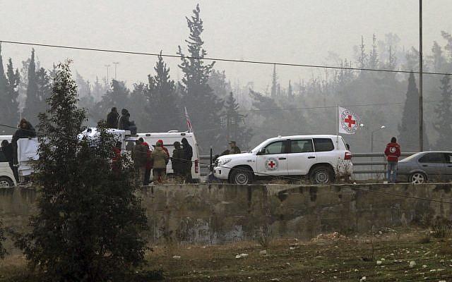 Des civils autours d'un véhicule de la Croix Rouge à Alep, le 16 décembre 2016. (Crédit : SANA via AP)