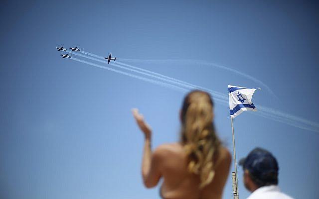 Des spectateurs admirent une équipe de voltigeurs israéliens survoler la ville de Tel Aviv, en Israël, le jeudi 19 avril 2018, pendant les célébrations du 70e Yom HaAtsmaout, anniversaire de l'indépendance d'Israël. (AP Photo/Ariel Schalit)