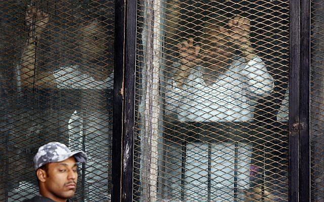 Illustration : des accusés égyptiens attendent leur condamnation depuis une cellule en verre insonorisée, dans le tribunal improvisé de la prison de Tora, au Caire, le 28 juillet 2018. (Crédit : AP/Amr Nabil)