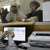 Une employée du gouvernement nommée par le Hamas à Gaza signe un document pour obtenir 50 % de son salaire qui aurait dû être versé depuis longtemps sur des fonds donnés par le Qatar, tandis que d'autres attendent dans la queue, au bureau de poste principal de Gaza, à Gaza City, le 7 décembre 2018. (AP Photo/Adel Hana)