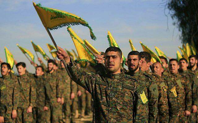Des combattants du Hezbollah brandissent des drapeaux lors d'une commémoration de Sheik Abbas al-Mousawi, leader du mouvement qui avait été tué dans une frappe aérienne israélienne en 1992, dans le village de Tefahta, au sud du Liban, le 13 février 2016 (Crédit : Mohammed Zaatari/AP)