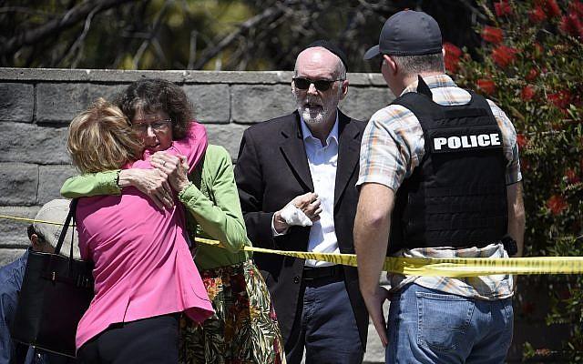 Deux personnes se réconfortent mutuellement aux abords de la synagogue Habad de Poway, en Californie, après une fusillade, le 27 avril 2019 (Crédit : AP/Denis Poroy)