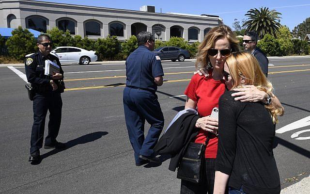 Jessica Parks, à droite, réconforte Tina White aux abords de la synagogue de Poway, en Californie, après une fusillade, le 27 avril 2019 (Crédit : AP/Denis Poroy)