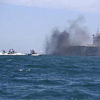 Sur cette photo de l'agence de presse iranienne semi-officielle, les bateaux des gardiens de la révolution prennent d'assaut une réplique de navire porte-avions américain pendant des exercices à grande échelle près de l'entrée du Golfe persique, le 25 février 2015 (Crédit :  AP/Fars News Agency, Hamed Jafarnejad)