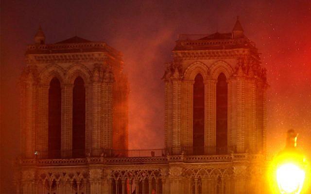 Les flammes illuminent le ciel alors que la cathédrale Notre-Dame brûle, le 15 avril 2019. (AP Photo / Thibault Camus)