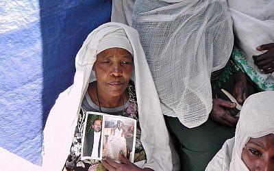 Une Ethiopienne à la synagogue d'Addis Abeba priant et tenant les photos de membres de sa famille vivant en Israël. (Crédit : Bernard Dichek/ Times of Israel)