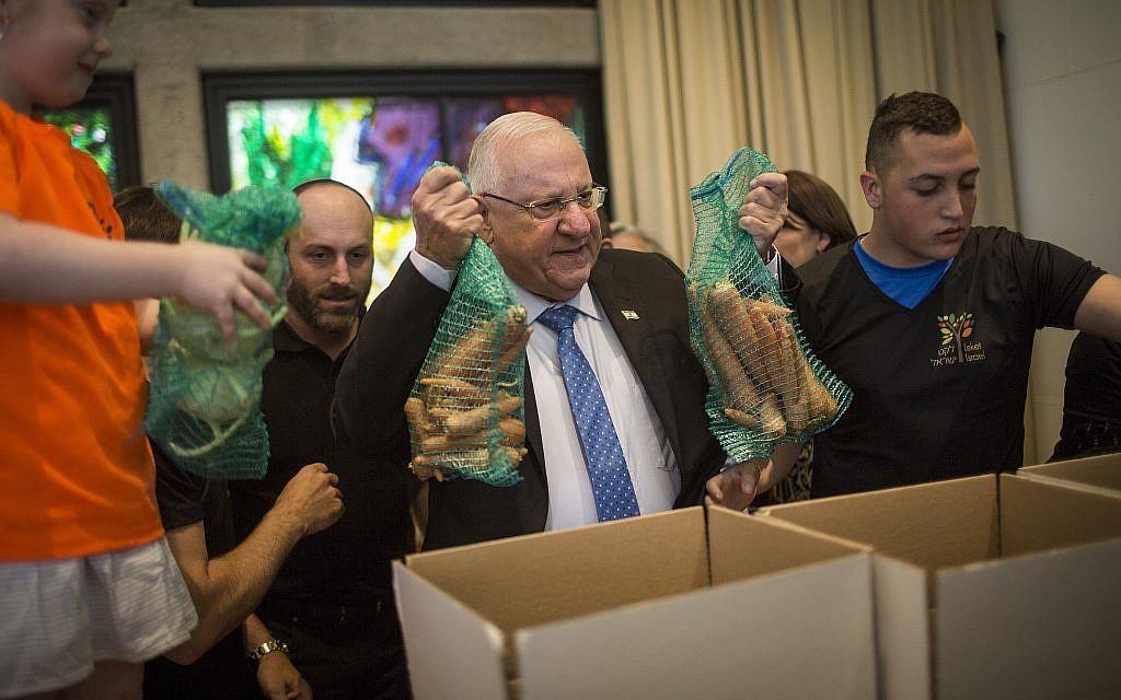 Le Président Reuven RIvlin aide des bénévoles à préparer des colis de nourriture pour les familles nécessiteuses avant Pessah, à la résidence du Président à Jérusalem, le 19 avril 2016. (Hadas Parush/Flash90/Fichier)