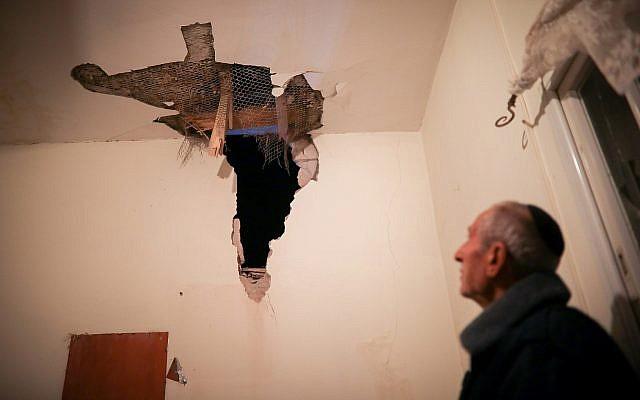 Un homme inspecte les dégâts causés à sa maison par une roquette tirée depuis la bande de Gaza, dans la ville de Sdérot, au sud d'Israël, près de la frontière avec Gaza, le 25 mars 2019. (Hadas Parush/Flash90)