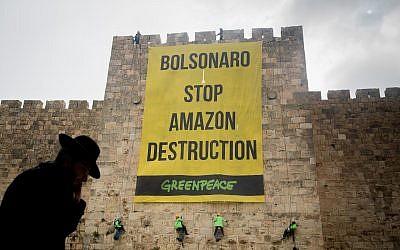 """Des militants de Greenpeace descendent en rappel les murs de la Vieille Ville de Jérusalem, lors d'une manifestation le 1er avril 2019, pour accrocher une banderole disant """"Bolsonaro Stop Amazon Destruction"""" pendant la visite du président brésilien Jair Bolsonaro en Israël. (Yonatan Sindel/Flash90)"""
