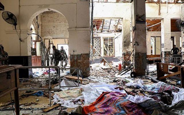 Des membres de services de sécurité du Sri Lanka marchent à côté de cadavres au sol parmi les débris de l'explosion au sanctuaire St Anthony, après l'exposition dans l'église à Kochchikade à Colombo, le 21 avril 2019. (ISHARA S. KODIKARA/ AFP)