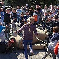 Cette photo prise le 19 avril 2019 montre des enfants en train de frapper avec des bâtons dune marionnette de Judas pour le Vendredi Saint, dans la ville de Pruchnik, en Pologne. (Hubert Lewkowicz / AFP)