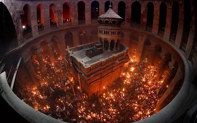 Des fidèles chrétiens orthodoxes tiennent de cierges allumés du le Feu sacré alors qu'ils se rassemblent dans l'Eglise du Saint Sépulcre dans la Vieille ville de Jérusalem, le 27 avril 2019 pour la Pâque orthodoxe. (THOMAS COEX / AFP)