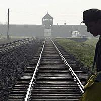 Dans cette photo du 29 juillet 2016, un homme traverse la tristement célèbre voie ferrée de l'ancien camp de la mort nazi d'Auschwitz-Birkenau en Pologne. (AP Photo/Alik Keplicz, FILE)