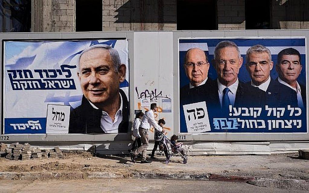 """Des gens passent devant des affiches de la campagne électorale montrant le Premier ministre Benjamin Netanyahu, à gauche, et les dirigeants de Kakhol lavan, de gauche à droite, Moshe Ya'alon, Benny Gantz, Yair Lapid et Gabi Ashkenazi, à Tel Aviv, le 3 avril 2019. Sur les affiches on peut lire, à gauche, """"Un Likud fort, un Israël fort"""" et, à droite, """"Chaque vote compte, victoire pour Kakhol lavan"""". (AP Photo/Oded Balilty)"""