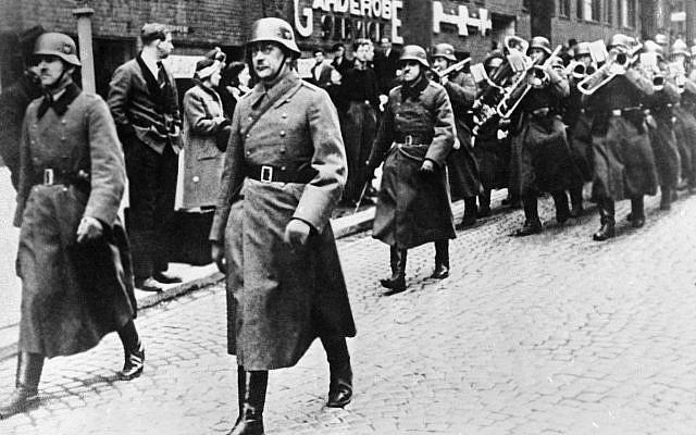Des civils norvégiens observent l'entrée des soldats allemands, menés par un orchestre, dans la capitale norvégienne d'Oslo, le 12 avril 1940 (AP Photo).