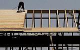 Un employé sur un toit d'un chantier à Jérusalem le 5 août 2015. (Nati Shohat/Flash90)