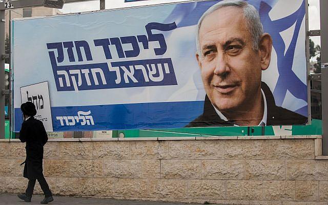 Un homme passe devant une affiche de la campagne électorale de Benjamin Netanyahu, Premier ministre et chef du parti du Likud à Jérusalem le 2 avril 2019. (Crédit : Yonatan Sindel/Flash90)