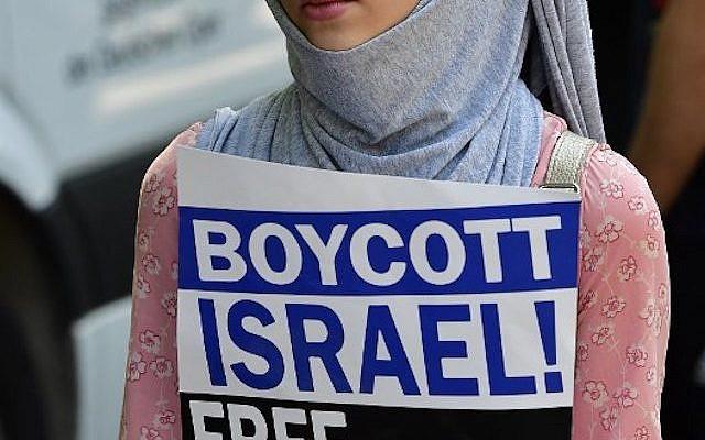 """Une manifestante tenant un écriteau """"Boycott d'Israël, Libérez la Palestine"""" lors de journée Al-Qods à Berlin, le 9 juin 2018. (AFP PHOTO / Tobias SCHWARZ)"""