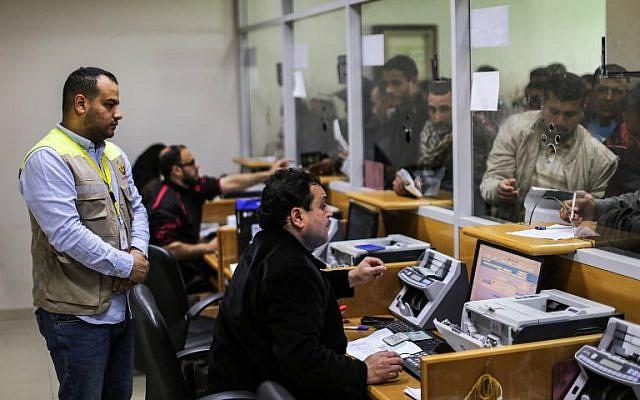 Des employés aident les Palestiniens à recevoir l'aide financière apportée par le Qatar aux familles défavorisées au bureau central de poste de Gaza City, le 26 janvier 2019 (Crédit : Mahmud Hams/AFP)