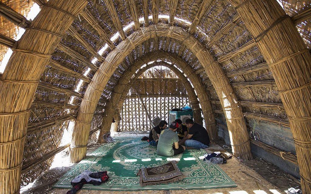 Des touristes assis dans une maison maison flottante faite de roseaux et de palmes de dattiers, en Irak, le 29 mai 2019. (Crédit : Hussein FALEH / AFP)