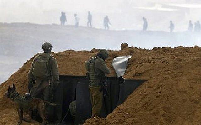 """Des soldats israéliens se rassemblent sur une position le long de la frontière avec la bande de Gaza, près du kibboutz de Nahal Oz, au sud d'Israël, le 30 mars 2019, alors que des Palestiniens (en arrière-plan) manifestent pour le premier anniversaire des manifestations de """"La Marche du retour"""". (Jack Guez/AFP)"""