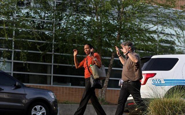Des étudiants et des professeurs quittent les bâtiments avec les mains en l'air après une fusillade sur le campus de l'Université de Caroline du Nord, Charlotte, à University City, Charlotte, le 30 avril 2019.(Crédit : Logan Cyrus / AFP)