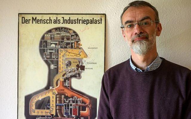 """Le responsable de l'Institut d'anatomie de l'école de médecine du Brandenbourg, Andreas Winkelmann, pose près d'une affiche de 1926 détaillant le corps humain comme un """"palais industriel"""", avril 2019. (Crédit : MACDOUGALL / AFP)"""