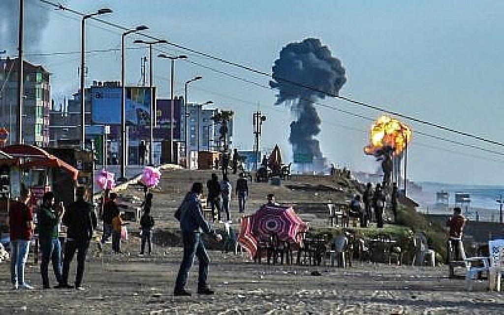 Des Palestiniens se réunissent sur la plage de Gaza City alors que des fumées et des flammes s'élèvent suite aux attaques israéliennes qui ont suivi les tirs de roquette des groupes terroristes palestiniens, le 4 mai 2019 (Crédit : Sami al-Sultan/AFP)